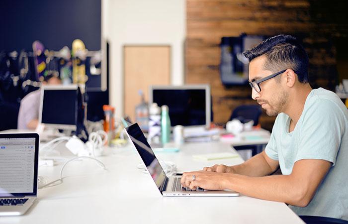 Web designer on laptop designing website in Dublin office
